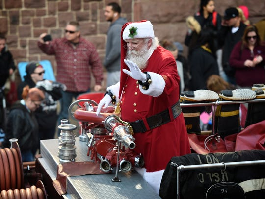 Santa greets the crowds coming out to enjoy the annual holiday parade a week later than usual due to a weather postponement.