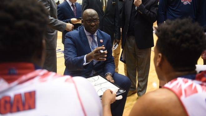 Detroit Mercy head basketball coach Bacari Alexander instructs his players during a timeout.