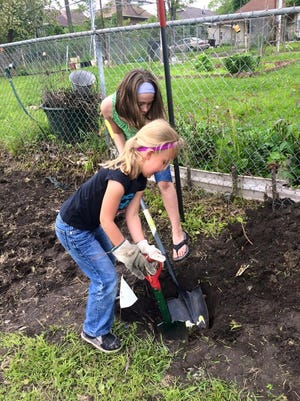 Isabelle Raymer, 5, of Des Moines shovels with Norah Nidey, 9, of Des Moines at the groundbreaking event for the Forest Ave Community Orchard in Riverbend at 334 Forest Ave. on Saturday morning.