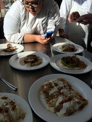Jameelia Ricks looks at the dishes she and her Culinary 102 classmates prepared at Coltivare.