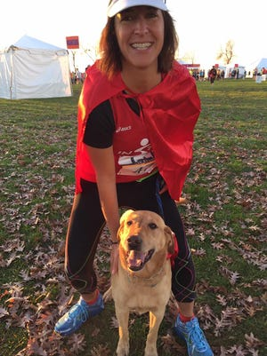 """This 10-year-old Lab, Louie, ran his first marathon Sunday with his owner, Heather Berken, and they wore capes together as the """"Dynamic Duo."""""""