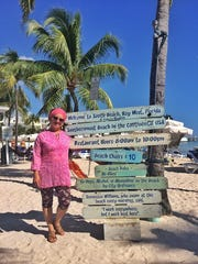 Alison Miller stands by a sign in Key West, Florida.