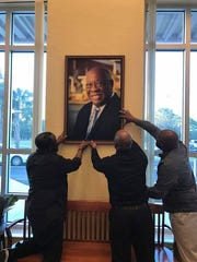 Jon David Anderson (from left), David Anderson II and Kristopher Anderson, the sons of Dr. David L. Anderson, hang their father's picture in the administration office of his namesake middle school.
