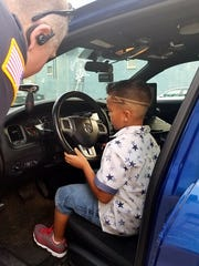 Orion Clark sits inside the police vehicle of RPD Officer