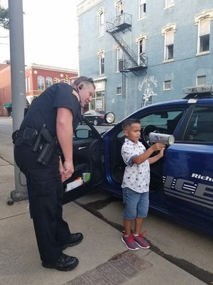 Orion Clark points a radar gun under the supervision of RPD Officer Jeremy Worch. Clark, who is 7, wants to become a police officer.