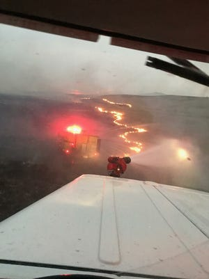 Local volunteer firefighters work on putting out the Alice Creek fire when it exploded out of the national forest onto private ground in Lewis and Clark County Saturday and Sunday.
