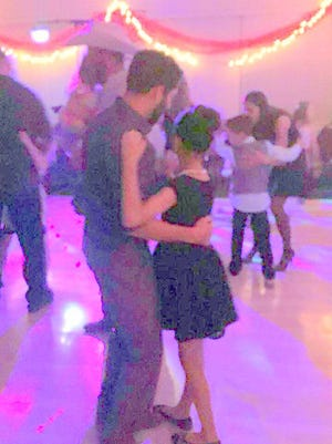 A father dances with his daughter at the family dance.