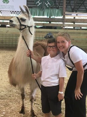 Teen leader Lauren Tomasek, 19, stands with 4-H Extraordinary Explorers member James Ursitti, 10, at an animal showing.