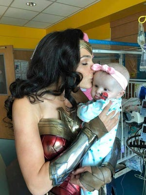 """Wonder Woman"" star Gal Gadot holds Karalyne Sahady during a surprise visit to Inova Children's Hospital in Falls Church, Va., on Friday."