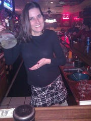Amy Stevenson poses behind the bar of her establishment,