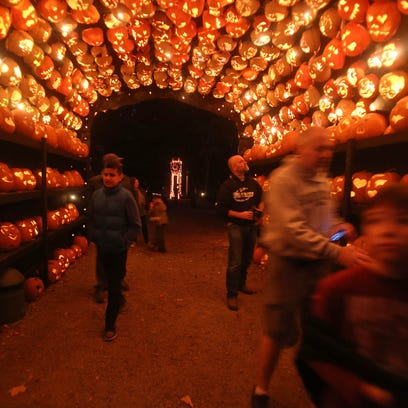 People make their way through a tunnel of Jack O'Lanterns
