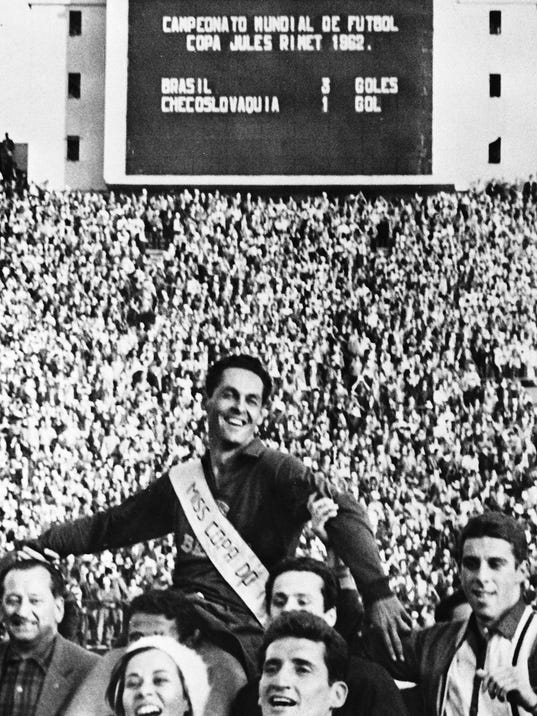 FILE - In this June 17, 1962 file photo, Brazil's goalkeeper Gilmar is held aloft by supporters, after Brazil defeated Czechoslovakia in the World Cup final soccer match, in Santiago, Chile. On this day: Brazil defeated Czechoslovakia three goals to one to defend the trophy it had won four years earlier in Sweden. (AP Photo/File)