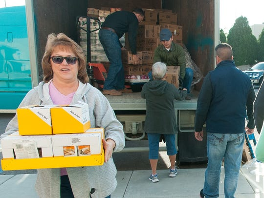 Karen Altamirano, of Steinborn & Associates Real Estate, carries food items  Tuesday while volunteering with Las Cruces Home Builders Association's annual Thanksgiving dinner delivery. Volunteer Tom Herbeck, right, is representing Veloz Homes.