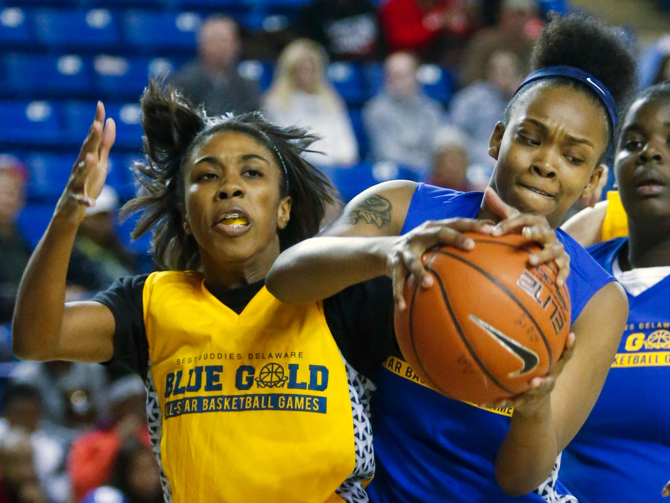 Gold's Rajene Bowe of Milford fights for a rebound with Blue's Al'kirah Wilson of A.I. du Pont in the second half of the Blue-Gold All-Star Basketball game at the Bob Carpenter Center Saturday. Blue won, 66-54.