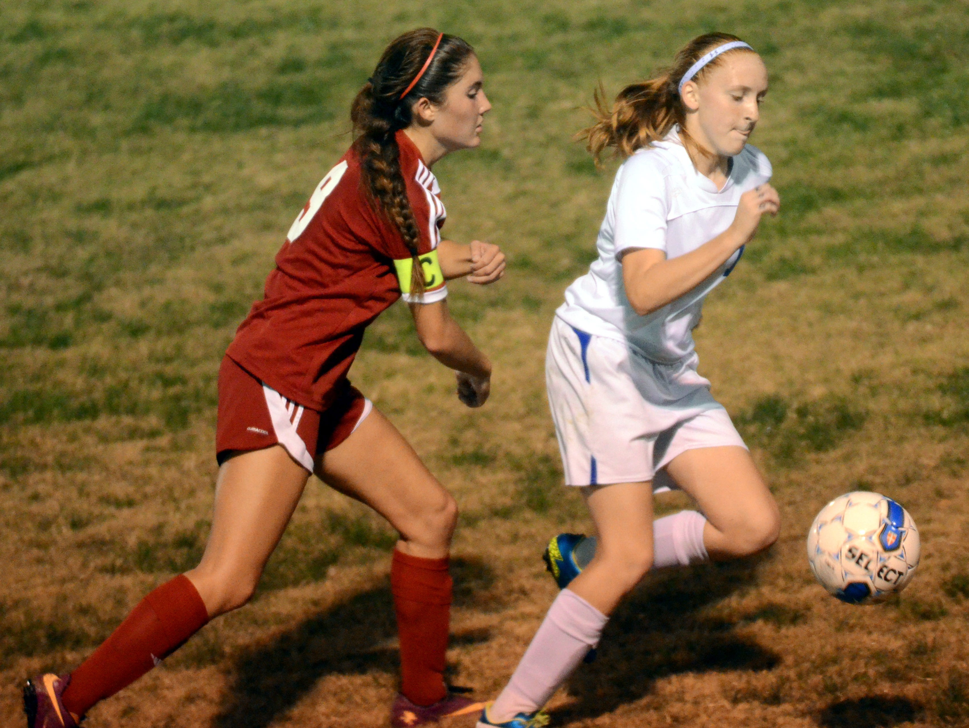 White House High sophomore forward Madisson Davis runs on to a ball played up the sideline as Page junior Sydney Strock pursues. Davis scored all three White House goals in the first half of Saturday evening's sectional loss.