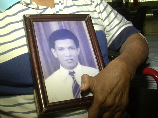 Edward Alwis holds a picture of himself.