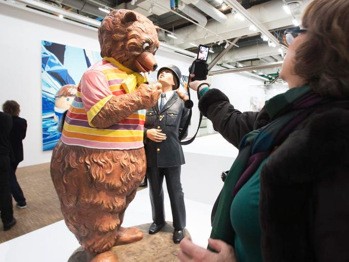 """A visitor takes pictures of """"Bear and Policeman 1988"""