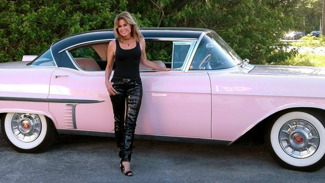 Cindy Goetz, who has won two pink Cadillac awards as one of Mary Kay's top salespeople, poses in front of Elvis' Mary Kay pink 1957 Cadillac which underwent a two-year renovation by Vero's Dale Warrington.