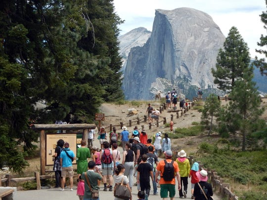 This August 5, 2015 photo shows tourists walking out to Glacier Point with a background view of Half Dome at Yosemite National Park.