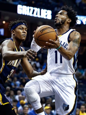 Memphis Grizzlies guard Mike Conley (right) drives for a layup against Indiana Pacer defender Joe Young during first quarter action at FedExForum.