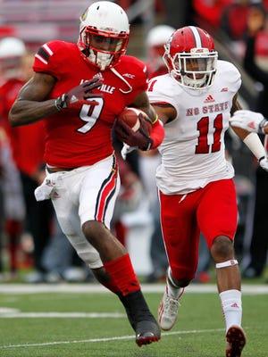 N.C. State's Juston Burris (11) chases after University of Louisville's DeVante Parker (9) at Papa John's Cardinal Stadium in Louisville, Kentucky.       October 18, 2013