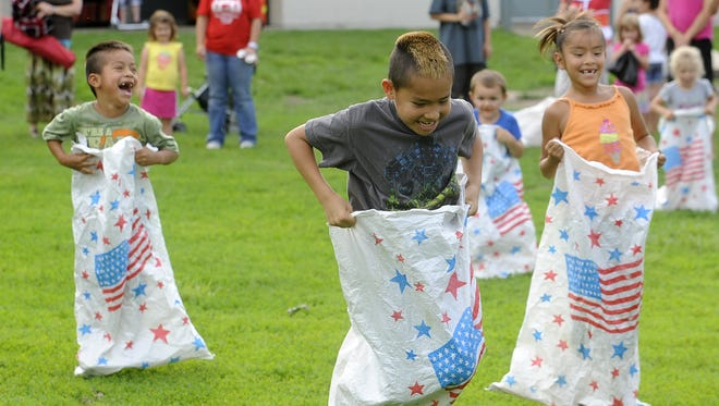 Wambli Stevens, Christian Arcoren and Maste Win Stevens take part in sack race during Kids' Nite in the Park at McKennan Park in Sioux Falls, S.D. Tuesday, June 25, 2013. (Emily Spartz / Argus Leader)