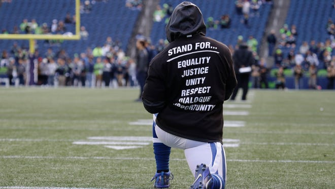 An Indianapolis Colts player kneels on the field Sunday, Oct. 1, 2017, during warmups before a game against the Seattle Seahawks in Seattle. The unidentified player is wearing a special team t-shirt in reference to recent protests during the singing of the national anthem at NFL games.