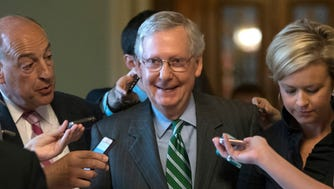 Senate Majority Leader Mitch McConnell smiles as he leaves the chamber after announcing the release of the Republicans' health care bill at the Capitol on Thursday.