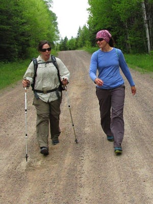 Heisz (left) and Koffarnus hike down a dirt road on the Ice Age Trail.