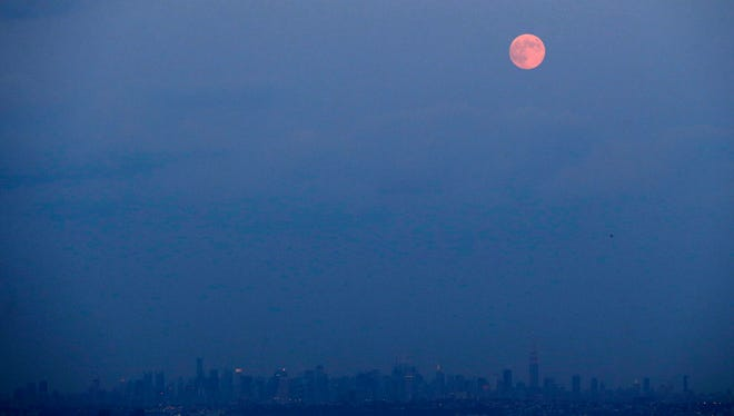 The moon rises over the New York skyline in its full stage under a phenomenon called the blue moon, as seen from West Orange, N.J., on Tuesday.