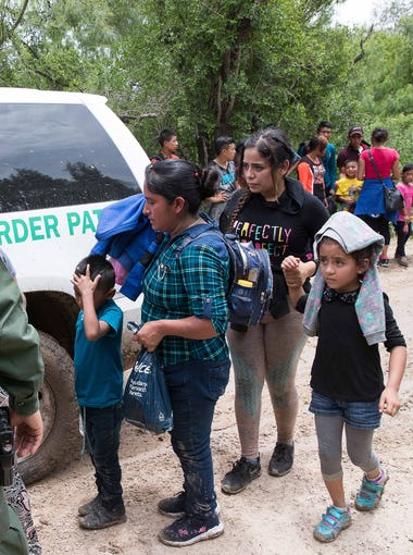 Border Patrol agents take a group of migrant families to a safer place to be transported after intercepting them near McAllen, Texas on June 19, 2018.