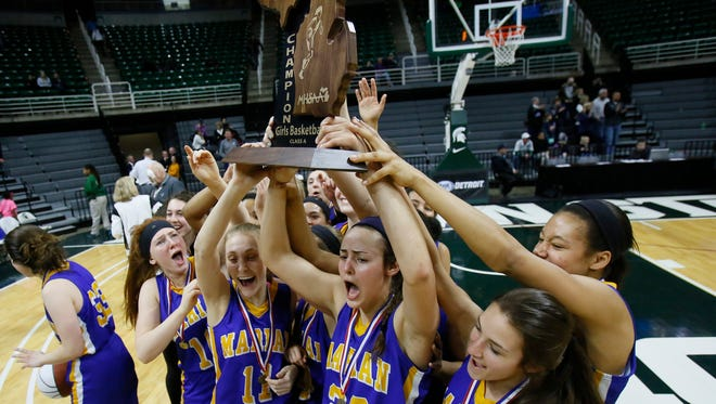 Bloomfield Hills Marian players celebrate for the Fox TV camera's with the championship trophy after their 51-37 win over Dewitt in MHSAA Class A girls basketball final on Saturday, March 21, 2015 in East Lansing.