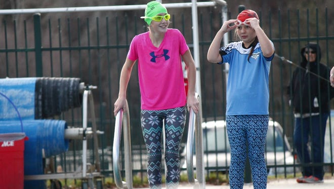 Ashley Effa, 13, left, and Katie Effa, 10, prepare to leap into the pool at the annual Polar Bear Plunge at the Redding Aquatic Center.