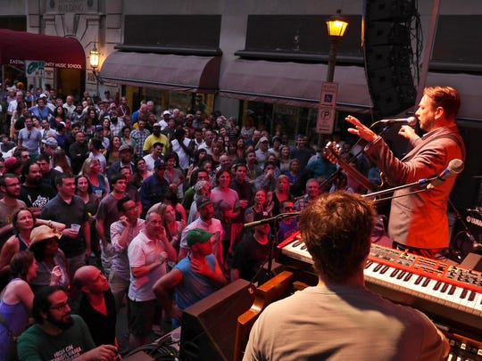 Eddie Roberts of the New Mastersounds talks to the crowd on a packed Jazz Street during their set at a past Rochester International Jazz Festival.
