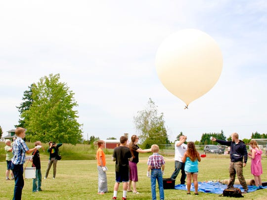 Evergreen School students launch a high altitude balloon June 7. A strong gust of wind broke the line between the balloon and the boxes of experiments. The team will try again June 20.