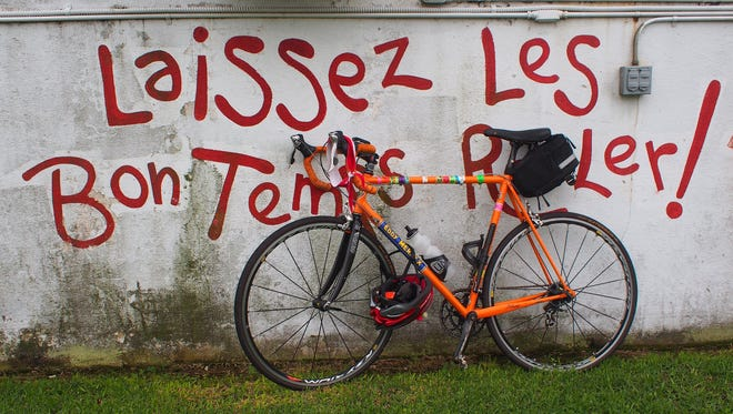"""A bike sits parked outside Fred's Lounge in Mamou, La., during the Cycle Zydeco bike tour April 27. The words behind it (which translate: """"Let the good times roll"""") capture the spirit of the tour."""
