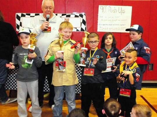 Following this year's Pinewood Derby on Friday at Walker Middle School, Cub Scouts Pack 141 Chairman Walt Smith announces the winners. Scouts, from left, are Logan Lorent, first place; Aidan O'Halloran, second place; Luke Costentano, third place; Nicholas Buset, Most Scout Spirit; Jayden Bollander, Best in Show; and Ethan Cox, Funniest Car.
