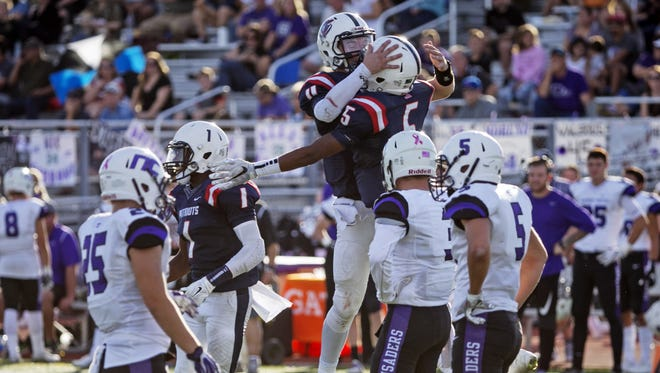 Queen Creek American Leadership Academy running back Jermiah Boyd (5) celebrates with quarterback Dallin Edwards after Boyd made a touchdown catch against Phoenix Northwest Christian during the third quarter of the 3A semifinal high school football game at Williams Field High School in Gilbert on Saturday, November 19, 2016. Queen Creek American Leadership Academy won the game 41-21.