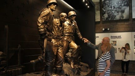"""WWII Veteran Joseph Farina and his wife, Elizabeth, look at the """"Leave No Man Behind"""" sculpture at the Hall of Heroes in New Windsor."""