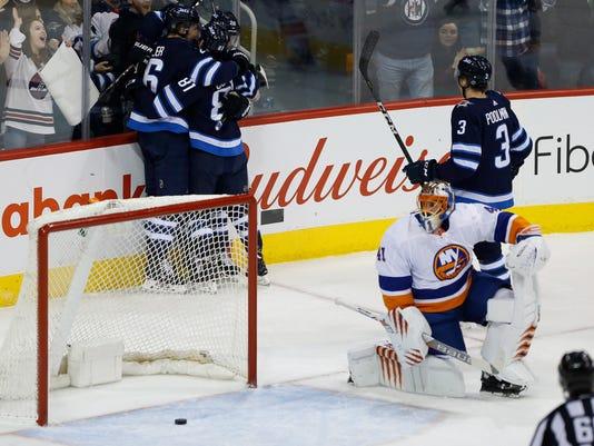 Winnipeg Jets' Blake Wheeler (26), Kyle Connor (81), Patrik Laine (29) and Tucker Poolman (3) celebrate Wheeler's goal as New York Islanders goalie Jaroslav Halak (41) looks on during first-period NHL hockey game action in Winnipeg, Manitoba, Friday, Dec. 29, 2017. (John Woods/The Canadian Press via AP)