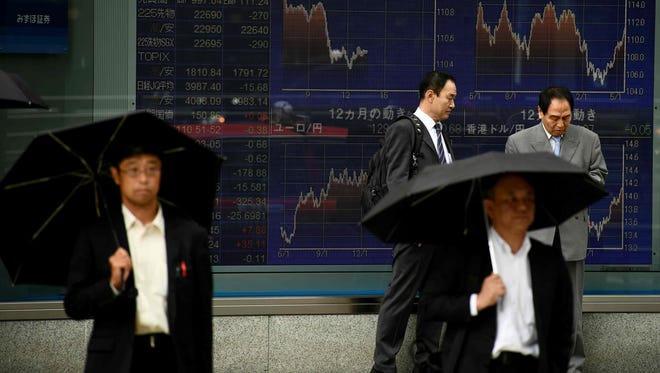 Pedestrians walk past a stock indicator showing stock prices of Japanese companies listed on the Tokyo Stock Exchange in Tokyo on May 23, 2018.