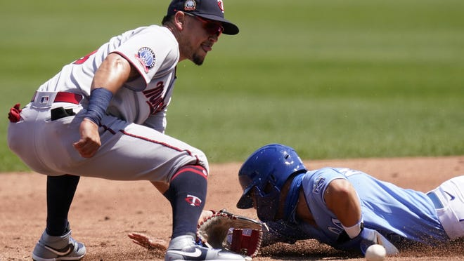 Kansas City Royals Whit Merrifield, right, beats the tag by Minnesota Twins second baseman Ildemaro Vargas, left, for a stolen base during the first inning of a baseball game at Kauffman Stadium in Kansas City, Mo., Sunday, Aug. 23, 2020.
