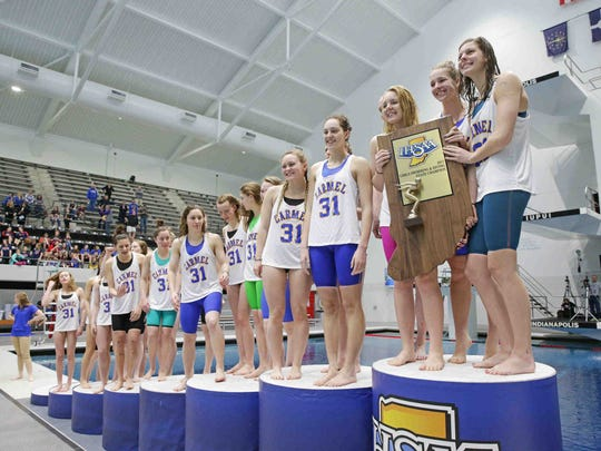 The Carmel Girls Swim Team is presented a trophy for winning the IHSAA girls swimming state finals, held at IUPUI Natatorium, Feb. 11, 2017.