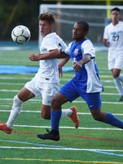 John Jay's Nicholas Zarrella, left, fights with Carmel's Ryan Hoo, right, for possession of the ball during Thursday's game at John Jay High School.