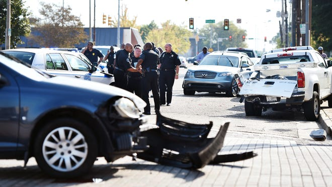 Jackson police officers stand amid the wreckage left after an auto theft and police pursuit ended in multi-vehicle accident in downtown Jackson.