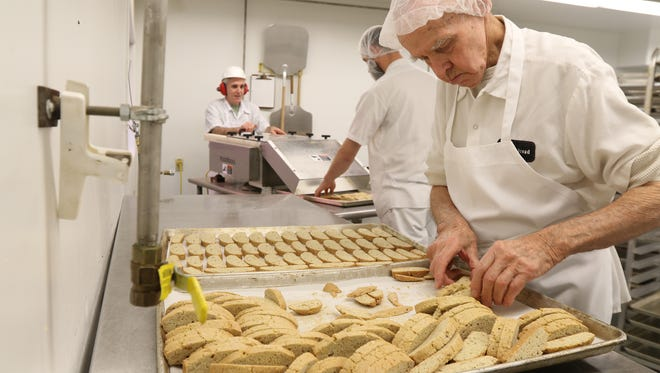 Brother Alberic Gardner, places the biscotti on trays for their second bake. Behind him, Brother Paul Richards puts the the biscotti loaf through a slicer to Brother Placid Larkin, who was collecting the cut pieces at the other end. The monks at the Abbey of the Genesee started a new specialty line of biscotti and fruit and nut bars earlier in the year.
