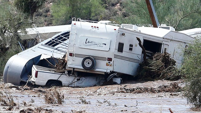An RV is piled atop a pickup and horse trailer as floodwater runs high in New River on Aug. 19. Phoenix firefighters were busy with calls about flooded cars and homes.