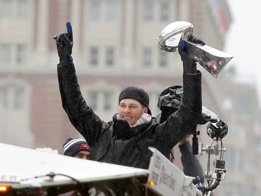 New England Patriots quarterback Tom Brady hoists the
