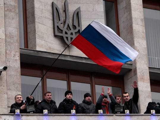 FILE - In this March 5, 2014 file photo, pro-Russia demonstrators holding a Russian flag, with the Ukrainian emblem in the background, stand on the balcony of the regional administrative building after storming it in Donetsk, Ukraine. With Crimea in Russia's pocket, the world anxiously awaits Russian President Vladimir Putin's next move. Protesters have seized administrative buildings in several eastern cities and hoisted Russian flags over them. Some clashed with supporters of the Kiev government, raising the danger that the Kremlin could use violence as a pretext to send in troops. (AP Photo/Sergei Chuzavkov, File)