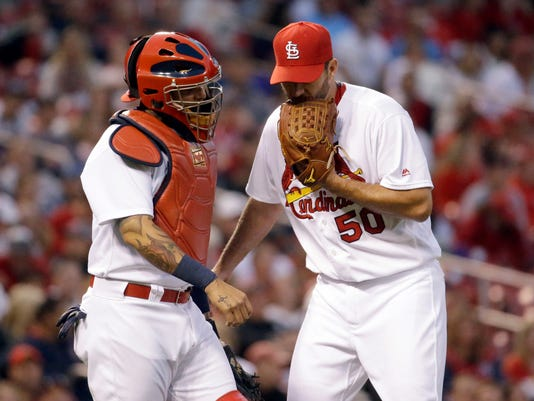 St. Louis Cardinals starting pitcher Adam Wainwright, right, and catcher Yadier Molina talk during the third inning of a baseball game against the Colorado Rockies on Wednesday, May 18, 2016, in St. Louis. (AP Photo/Jeff Roberson)